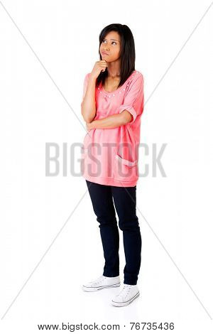 Full length pensive woman with hand under chin.