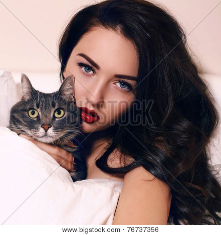Portrait Of Beautiful Girl With Dark Hair Posing With Cat