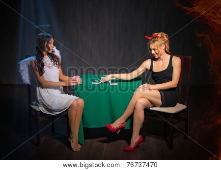 Angel and devil playing cards at room