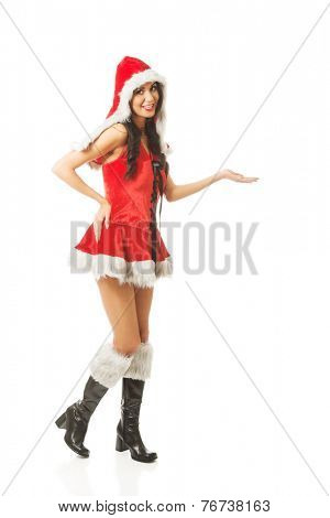 Full length woman holding something invisible in right hand wearing santa clothes .