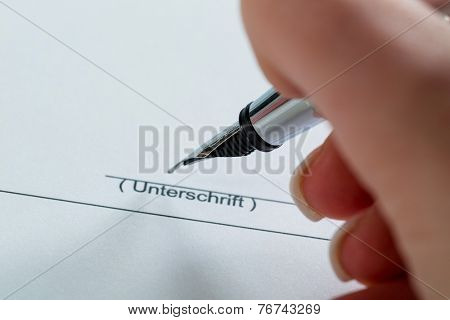 a hand with a fountain pen in the untrerschrift under a contract or testament.