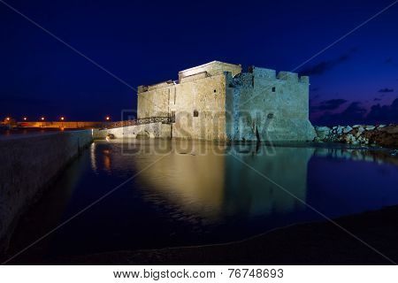 Illuminated Paphos Castle located in the city harbour at night with reflection in the water, Cyprus.