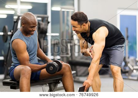 middle aged personal trainer training client in gym