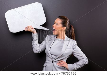 cute woman screaming in blank speech bubble isolated on black background