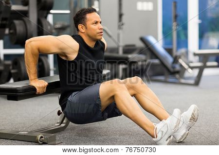 middle aged man stretching in gym