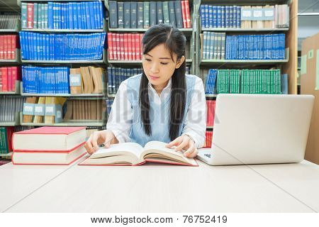 Student With Open Book Reading It In College Library