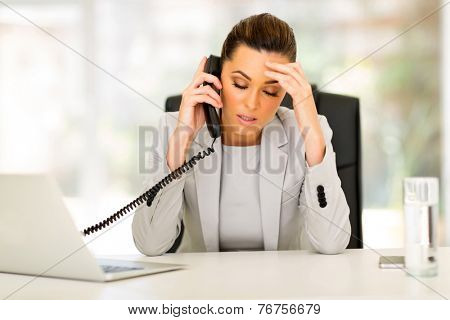 stressed businesswoman talking on telephone in office