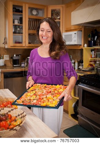 Woman Holding A Dryer Rack Of Tomatoes