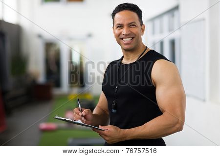 portrait of handsome mid age trainer holding clipboard