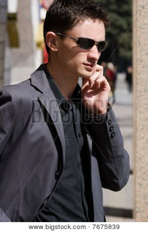 Businessman In Sunglasses Talks On His Mobile Phone