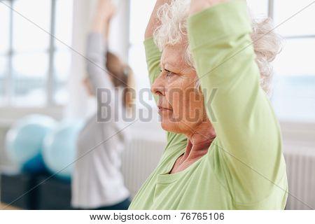 Senior Woman Practicing Yoga At Gym