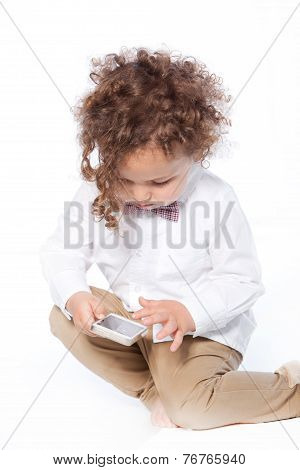 Curly Young Boy Swiping Mobile Phone