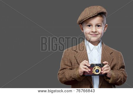 Cute boy with vintage photo camera on the grey background.