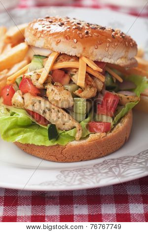 Chicken salad burger with french fries and fresh vegetables