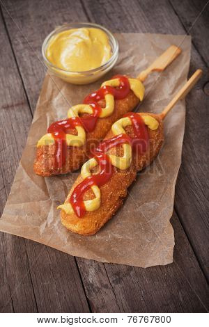 Corn dog, fried sausage in batter with mustard and ketchup
