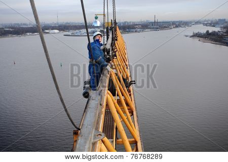 Installers Working At High Altitude, Erecting Tower Crane Lifting Construction.
