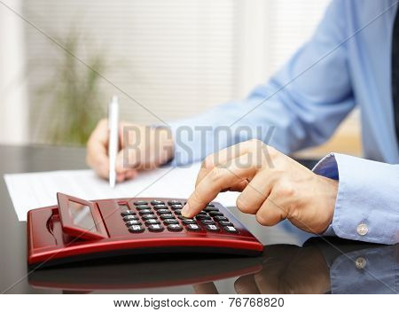 Businessman Working In  Office With Calculator And Fulfilling Documernt