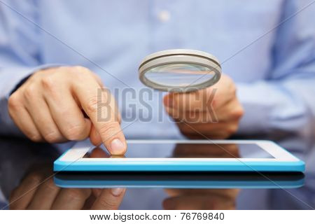 Businessman Using Tablet Computer  With Magnifying Glass . Caution In The Use Of Tablet Or Buying Ap