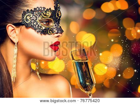 Sexy model woman with glass of champagne wearing venetian masquerade carnival mask at party, drinking champagne over golden holiday glowing background. Christmas, New Year celebration. Perfect make up
