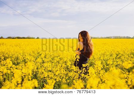 Rear view of young woman with long hair hugging herself on yellow blooming rapeseed field