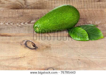 Ripe Green Avocado With Leaves On Wooden Background.