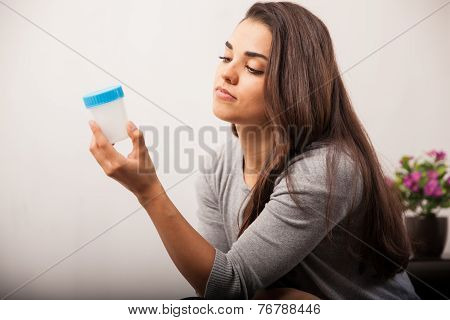 Woman Looking At Specimen Cup