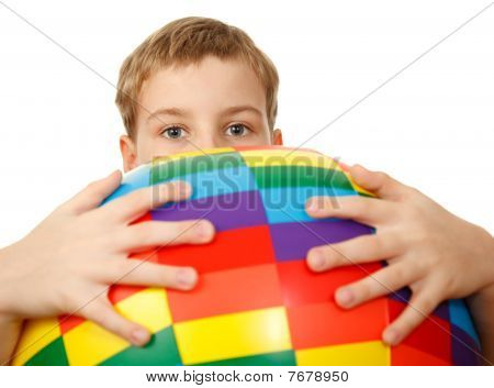 Boy holds in front of himself big multi-coloured inflatable ball