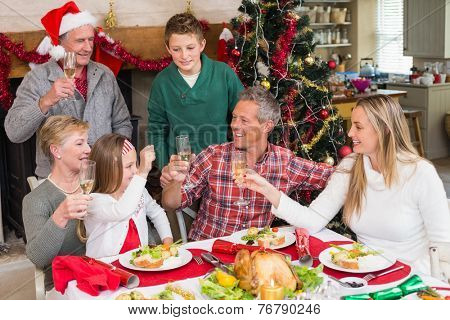 Family toasting each other at christmas at home in the living room