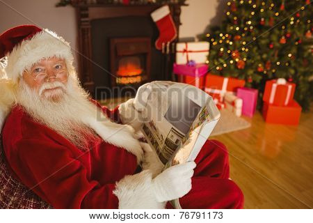 Smiling santa claus reading newspaper at home in the living room
