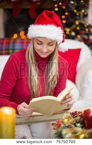 Pretty blonde in santa hat reading book at christmas time at home in the living room