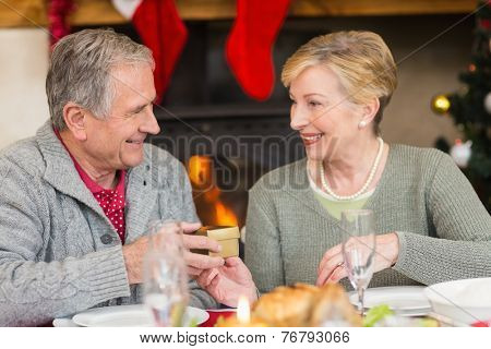 Senior man giving a christmas present to his wife at home in the living room