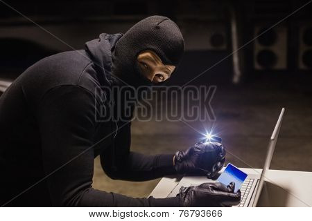 Robber shopping online while making light on black background