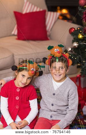 Smiling brother and sister in headband at home in the living room