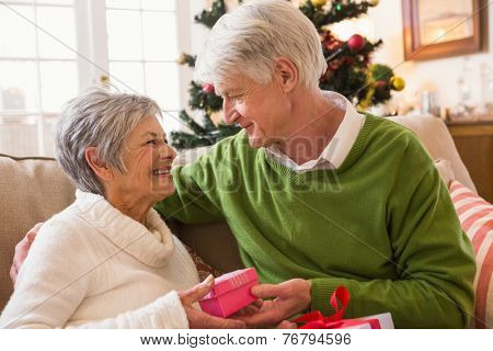 Senior couple exchanging christmas gifts at home in the living room