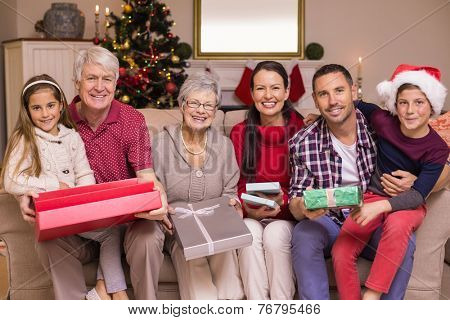 Happy extended family looking at camera at christmas time at home in the living room