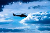 stock photo of attack helicopter  - Helicopter flying in the sky among the clouds - JPG