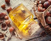 image of filbert  - Bottle of nut oil and basket with filberts on old kitchen table - JPG