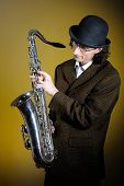 Постер, плакат: Портрет молодой английский джентльмен в котелок играет саксофон Жёлтый фон