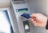 picture of plastic money  - man hand puts credit card into ATM - JPG