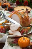 picture of kumquat  - Carving roasted turkey on a server tray garnished with fresh figs grape kumquat and herbs on fall harvest table - JPG