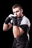 picture of kickboxing  - a young kickboxer or boxer isolated over a black background - JPG