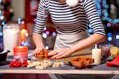 pic of christmas cookie  - Making ginger cookie on Christmas decorated table on festive lighting background - JPG