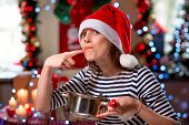 stock photo of finger-licking  - Woman tasting something licking her finger on Christmas - JPG