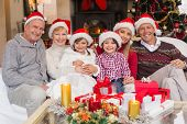 picture of extended family  - Happy extended family looking at camera at christmas time at home in the living room - JPG