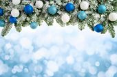 image of compose  - Winter or Christmas background composed of an arch of fresh snowy fir branches and bokeh lights with light blue copyspace - JPG