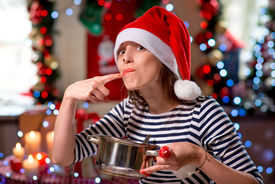 foto of finger-licking  - Woman tasting something licking her finger on Christmas - JPG