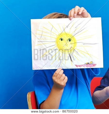 Child showing drawing with sun and ocean on a piece of paper