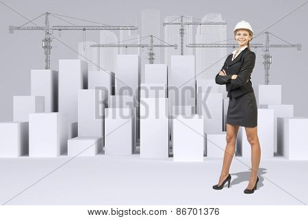 Business woman and white cubes with wire-frame buildings, tower cranes