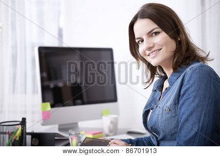 Happy Businesswoman At Her Desk Looking At Camera