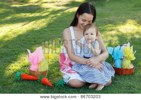 Two Smiling Sisters: Baby And Teen Girl With Chocolate Eggs For Easter